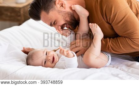 Cute Father Cuddling Bonding With Little Baby Daughter Spending Time Together Lying On Bed At Home.