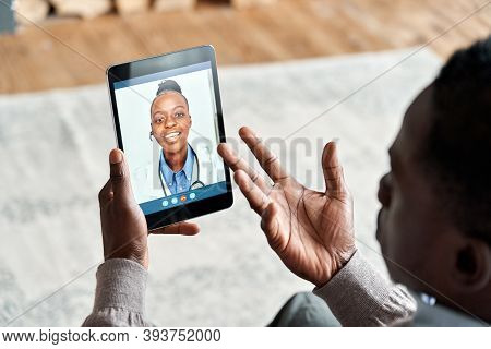 Over Shoulder View Of African Man Video Calling Female Virtual Doctor Consulting Patient On Tablet A