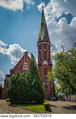 Beautiful, Red Brick Church With A Clock Tower, An Evangelical Augsburg Parish. Holy Trinity Church