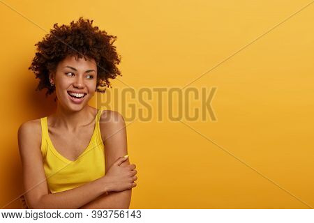 Optimistic Glad Millennial Girl Crosses Hands, Stands Shy And Expresses Positive Feelings, Has Tooth