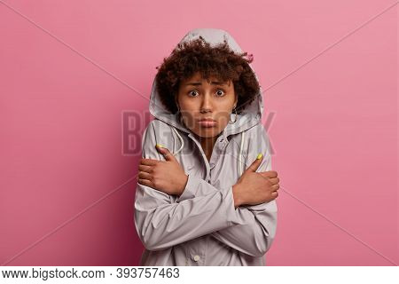 Portrait Of Dissatisfied Woman Crosses Hands Over Body, Feels Freezing After Walking During Wet Weat