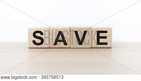 Save On Wooden Cubes On A Light Table. Money Saving And Taxes Saving Business Concept.