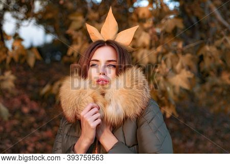 Beautiful Exquisite Girl Standing In The Park Freezing In A Jacket With Fur. Autumn Queen. Fall Seas
