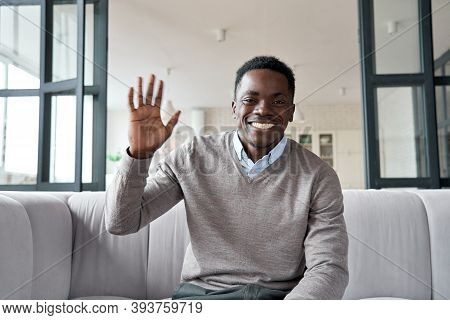 Happy African Young Man Online Teacher, Coach, Distance Worker Waving Hand Looking At Camera Or Web