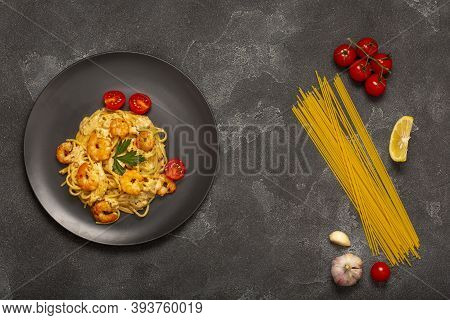 Spaghetti With Shrimps On A Gray Stone Background With Ingredients. Spaghetti, Tomatoes, Garlic, Lem