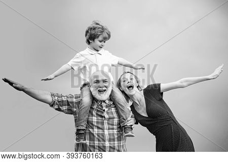 Grandson Sits On The Shoulders Of His Grandfather. Funny Time With Grandfather. Old And Young. Grand