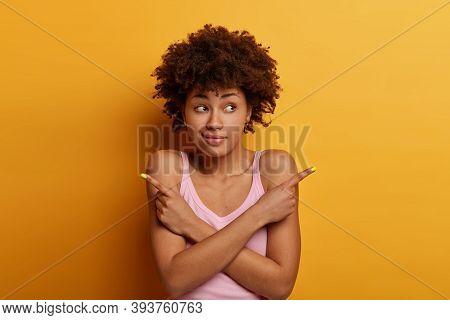 Doubtful Confused Dark Skinned Woman Points Sideways, Keeps Hands Crossed Over Body, Tries To Decide