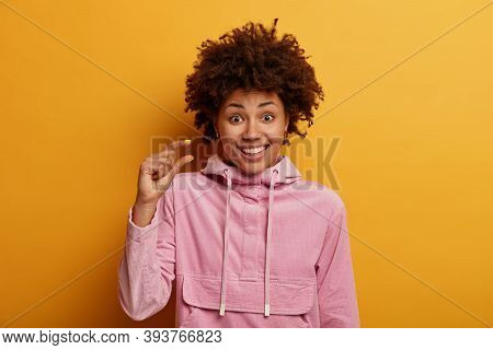 Positive Ethnic Millennial Girl Measures Tiny Object, Smiles Happily, Being In Good Mood, Tells Abou