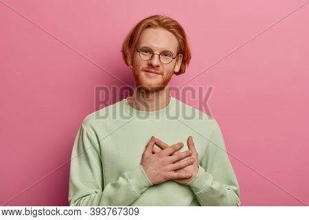 Portrait Of Thankful Ginger Man Presses Hands To Palms, Expresses Gratitude, Dressed Casually, Optic