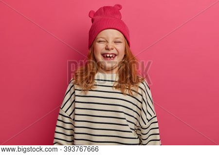 Children And Happiness Concept. Joyful Redhead Girl Laughs Out From Something Funny, Wears Pink Hat