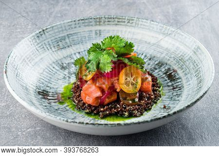 Delicate Fillet Of Salmon On A Cushion Of Quinoa With Vegetables, Avocado. Restaurant Menu Raw Salmo