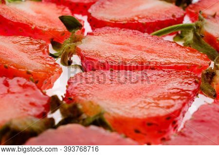 Ripe Strawberry Slices With Green Fresh Leaves On A White Background Close Up