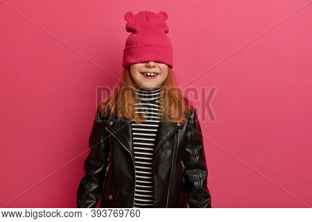 Studio Shot Of Lovely Redhead Girl Plays Hide And Seek Game, Waits For Surprise With Positive Emotio