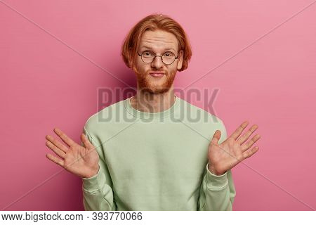 Indifferent Redhead Young Man Raises Palms, Feels Hesitant And Unaware, Says I Dont Care, Dressed Ca