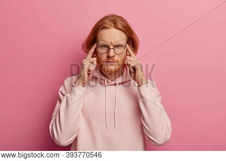 Portrait Of Intense Redhead Man Presses Index Fingers On Temples, Focused On Task, Tries To Concentr