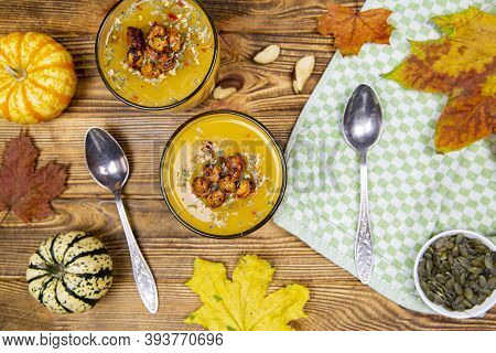 Delicious Pumpkin Soup On Brown Rustic Background, Top View. Thanksgiving Day Tasty Appetizer, Littl