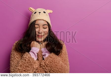 Studio Shot Of Pleasant Looking Asian Woman Pleased Hear Heartwarming Compliment, Keeps Eyes Closed,