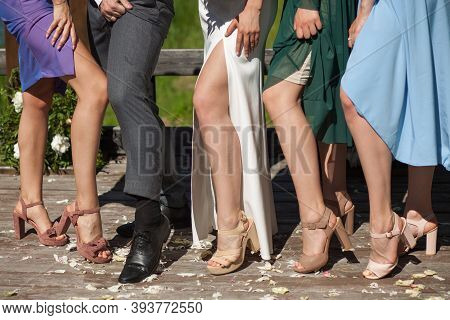 A Man In Trousers And Four Women In Open Dresses Show Their Legs In A Funny Way. Festive Party, Gues