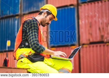 Professional Engineer Container Cargo Foreman In Helmets Working And Using Laptop Computer Checking