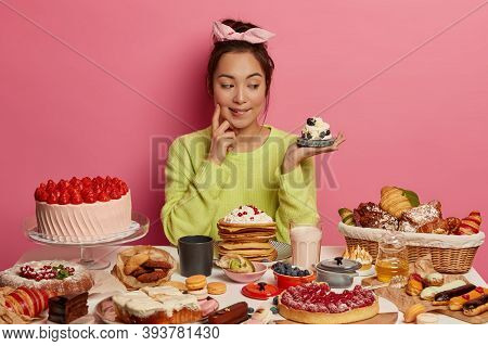 So Much Delicacy. Pretty Thoughtful Korean Woman Looks With Appetite At Tasty Creamy Dessert, Eats S