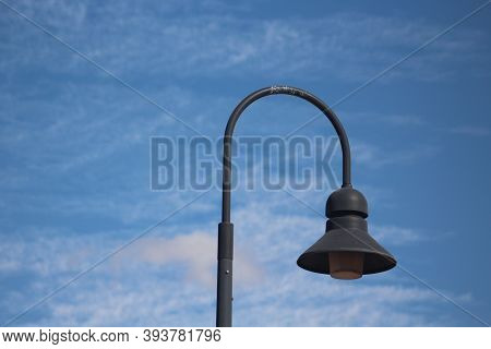 Curved Dark Gray Lamppost Against A Deep Blue Sky And Wispy White Clouds