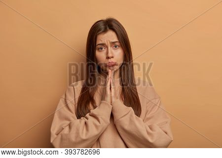 Miserable Gloomy Woman Pleads For Mercy, Keeps Palms Together, Makes Apologize, Purses Lower Lip, Ho