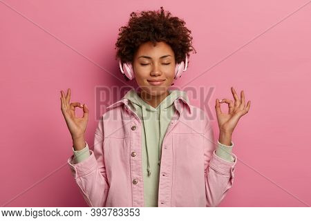 Relaxed Beautiful Woman Makes Zen Gesture, Meditates While Listens Peaceful Music In Headphones, Has
