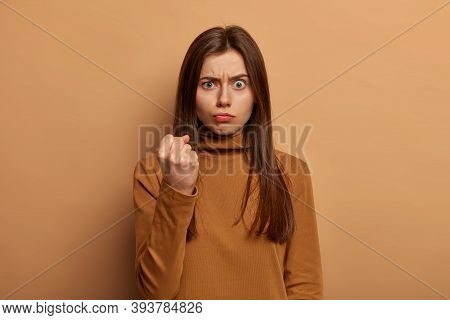 Photo Of Angry Woman Demonstrates Menace And Power, Raises Clenched Fist, Gives Warning Or Tries To