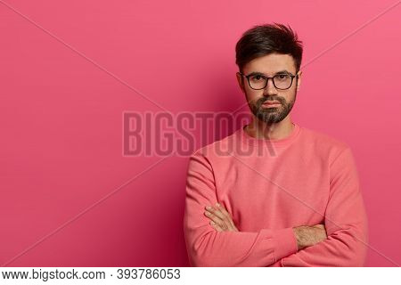 Self Confident Serious Bearded Man Stands With Arms Folded, Looks Seriously At Camera, Going To Disc