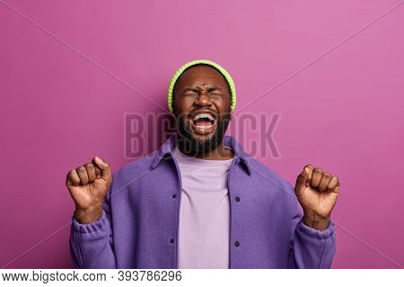 Photo Of Pleased Happy Hipster Man With Raised Fists, Has Fun At Party, Feels Overemotive, Being Joy