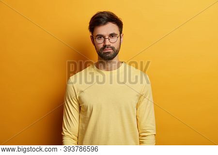 Photo Of Serious Looking Man Has Dark Bristle, Wears Round Spectacles And Yellow Jumper, Direct Gaze