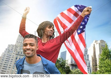 Young afro-american couple holding US flag, celebrating outside in the streets of New York City