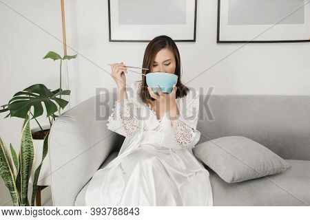 Asian Woman In White Satin Nightgown Sitting On A Gray Sofa And Eating Food During The Night. A Girl