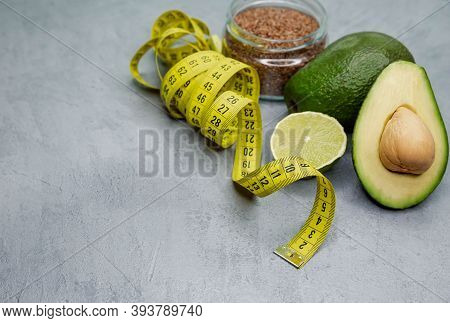 Fresh Avocado With Tape Measure On Grey Concrete Background. Healthy Lifestyle, Eating. Proper Nutri