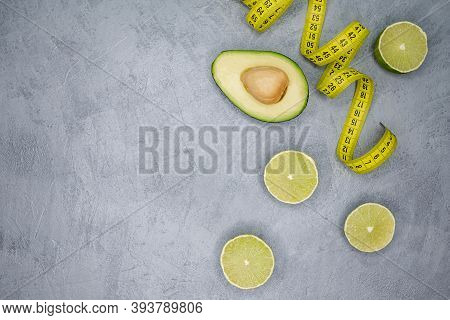 Raw Avocado Half With Tape Measure On Gray Background. Fresh Fit Avocado And Lime On The Grey Table.