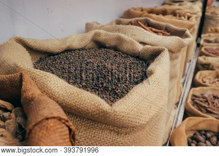 Various of Indian colorful powder spices on the market in India. Black pepper sack close up on the indian market