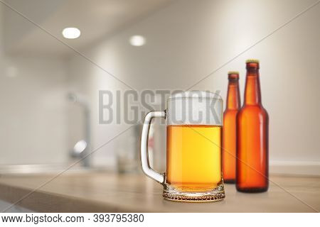 Full Beer Stein And Two Brown Bottles On The Kitchen Table.