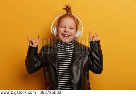 Happy Small Child Rocker Makes Horn Hand Sign, Rock N Roll Gesture, Enjoys Favourite Music Or Melody