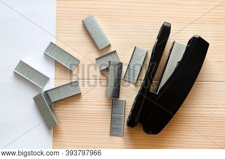 Stapler And Staples With Sheets Paper On Wooden Table. Close-up