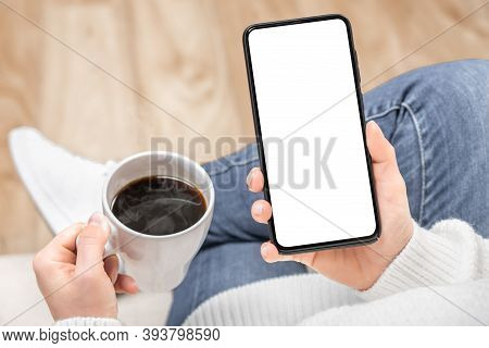 Mockup Image Of A Woman Holding And Using Black Mobile Phone With Blank Desktop Screen While Drinkin