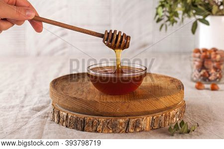 Brown Honey In A Glass Bowl On A Rustic Wooden Plate. The Wooden Spoon Drips Slowly.