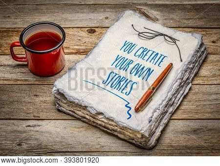 you create your own stories  inspirational note - handwriting in handmade paper sketchbook with cup of tea, creativity and personal development concept