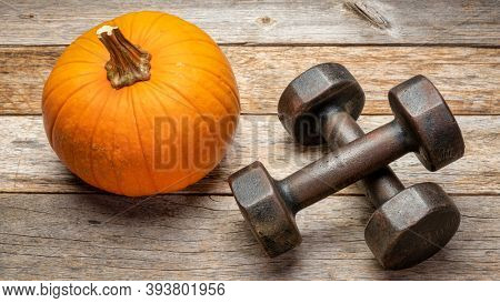 a pair of vintage iron rusty dumbbells on a rustic barn wood background with a pumpkin, fitness during fall holidays concept