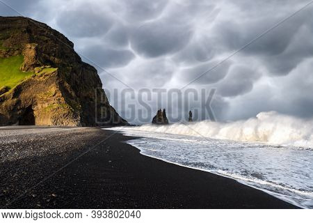 Incredible view on Black beach and Troll toes cliffs in cloudy weather. Stormy sky with menacing mammatus clouds on background. Reynisdrangar, Vik, Iceland. Landscape photography