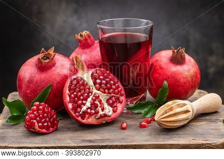 Ripe pomegranate, half a juicy pomegranate and healthy pomegranate juice in a glass on a cutting board, side view, dark vintage background.