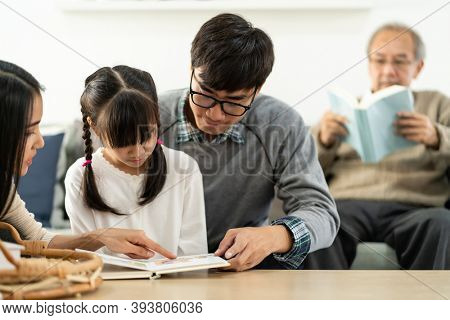 Asian cute girl reading story cartoon book with her mom and dad in living room with grandfather reading fiction book in background. Happiness multigenerational family and domestic lifestyle concept.