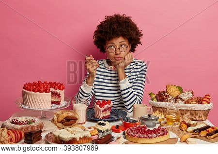 Pensive Dark Skinned Woman Thinks About Weight Gain While Eats High Calories Creamy Cake, Enjoys Swe
