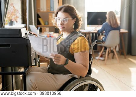 Young disable female office worker or secretary looking through paper while sitting by xerox machine and making copies against colleague