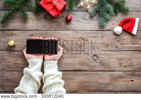 Hands Holding Smart Mobile Phone On Wooden Background With Christmas Decor, Pine Branches And Christ
