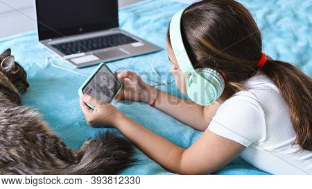 A Child With Headphones Playing A Computer Game On The Phone, The Cat Is Sleeping. A Little Girl Lie